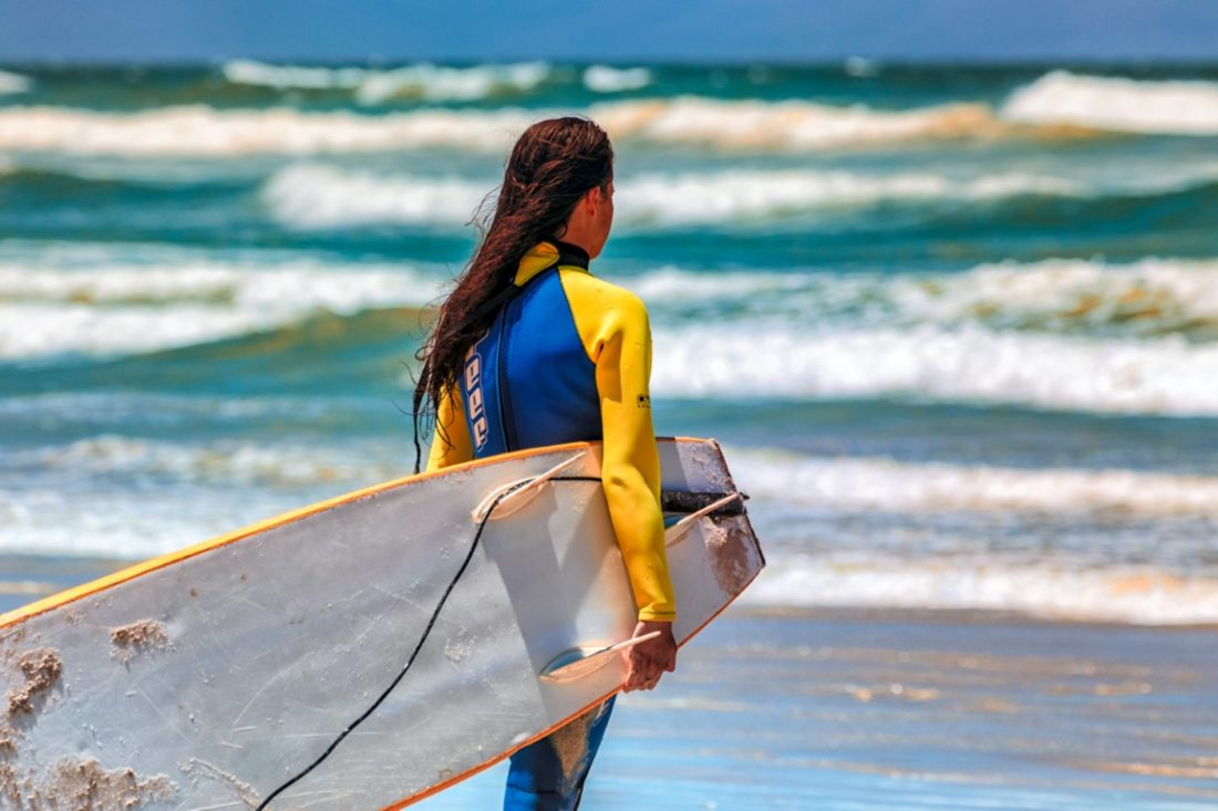 Girl on beach with surfboard
